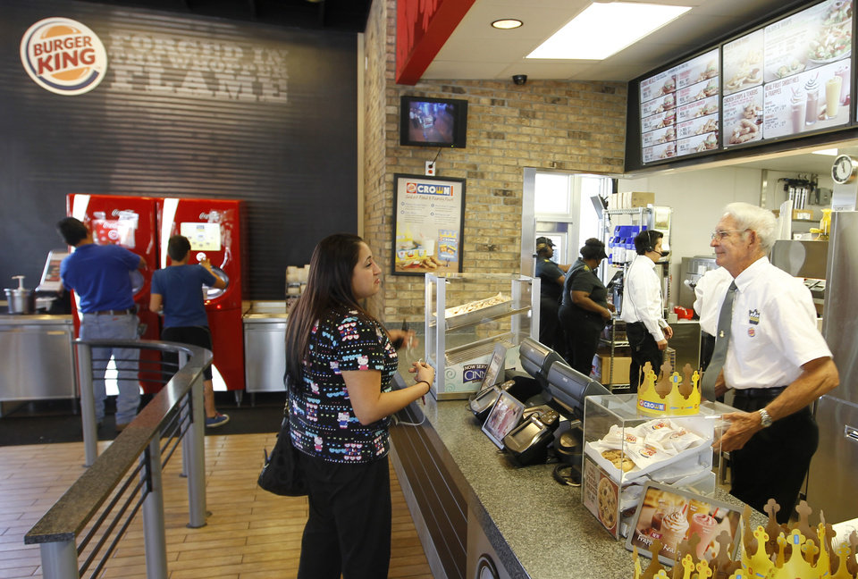 Photo -   In this March 28, 2012 photo, Jenny Vega orders food at a Burger King restaurant in Miami. Burger King launches 10 menu items including smoothies, frappes, specialty salads and snack wraps in a star-studded TV ad campaign. It's the biggest menu expansion since the chain opened its doors in 1954. (AP Photo/Luis M. Alvarez)