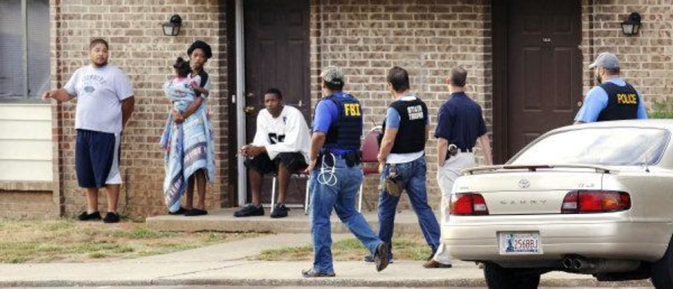 Residents look on as agents with the Edmond Police Department, FBI, and the Oklahoma Highway Patrol execute  search warrants at Rolling Green Apartments, 400 E. Danforth in Edmond. Photo by Paul B. Southerland, The Oklahoman ORG XMIT: KOD <strong>PAUL B. SOUTHERLAND - PAUL B. SOUTHERLAND</strong>