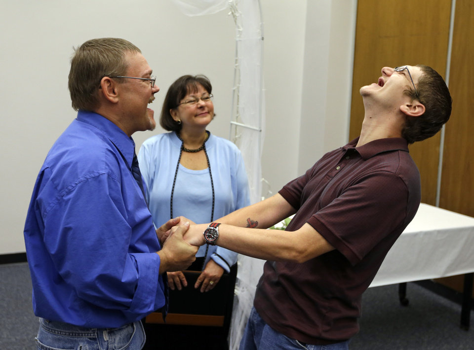 Photo - Adam Shoffner, right, shouts his joy after he married Daniel Tolliver, left, as Marion County Clerk Beth White looks on as same sex couple continued to be married for the second day in Indianapolis, Thursday, June 26, 2014. A federal judge struck down Indiana's ban on same-sex marriage Wednesday in a ruling that immediately allowed gay couples to wed. (AP Photo/Michael Conroy)