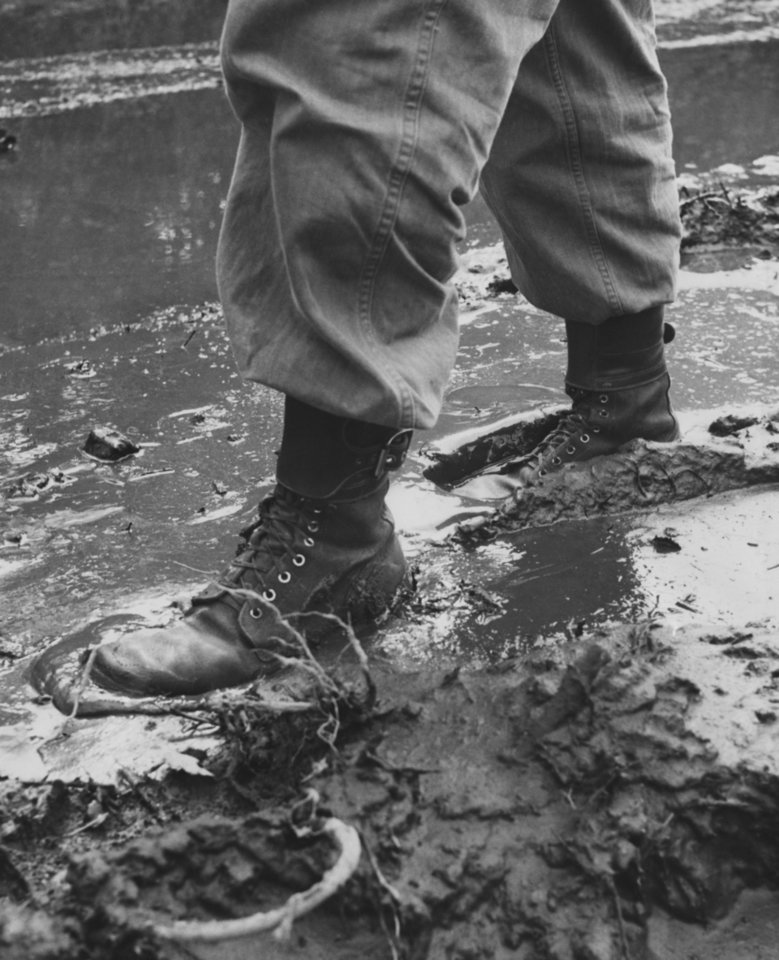 Photo - The worst enemy of the infantry takes its toll of carefully kept boots as Thunderbirds slosh through Hokkaido's muddiest month.  Photo by Ron Pyer of 45th Division News Photo.  Original dated 10/13/1951.  Published in The Daily Oklahoman 10/14/1951.
