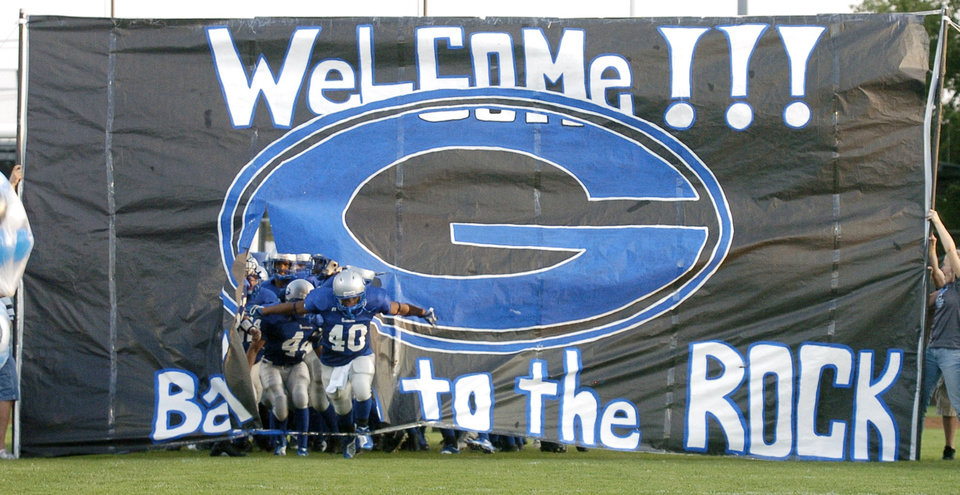 Photo - Guthrie football players, led by running back Kris King, run through a banner on their way onto the Jelsma Stadium field for their first game at the stadium in two years, prior to the Guthrie vs Shawnee high school football game at Jelsma Stadium in Guthrie, Okla., August 31, 2006. The Rock is the nickname for Jelsma Stadium. By Matt Strasen, The Oklahoman ORG XMIT: KOD
