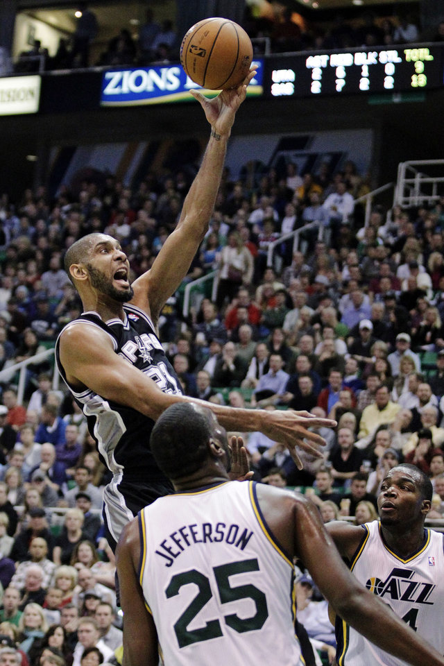 Photo - San Antonio Spurs forward Tim Duncan (21) lays the ball up against Utah Jazz center Al Jefferson (25) and forward Paul Millsap (24) in the first quarter during an NBA basketball game, Wednesday, Dec. 12, 2012, in Salt Lake City. (AP Photo/Rick Bowmer)