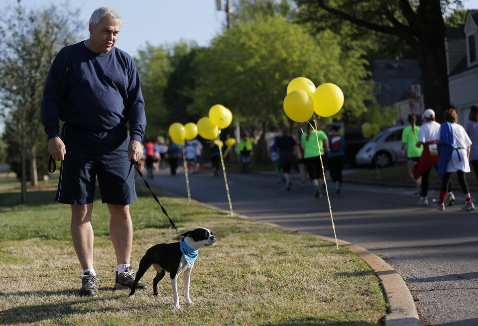 Kerry Laws and his dog, Trudy, watch runners along Shartel at Gorilla Hill during the Oklahoma City Memorial Marathon in Oklahoma City, Sunday, April 28, 2013.  Photo by Garett Fisbeck, For The Oklahoman