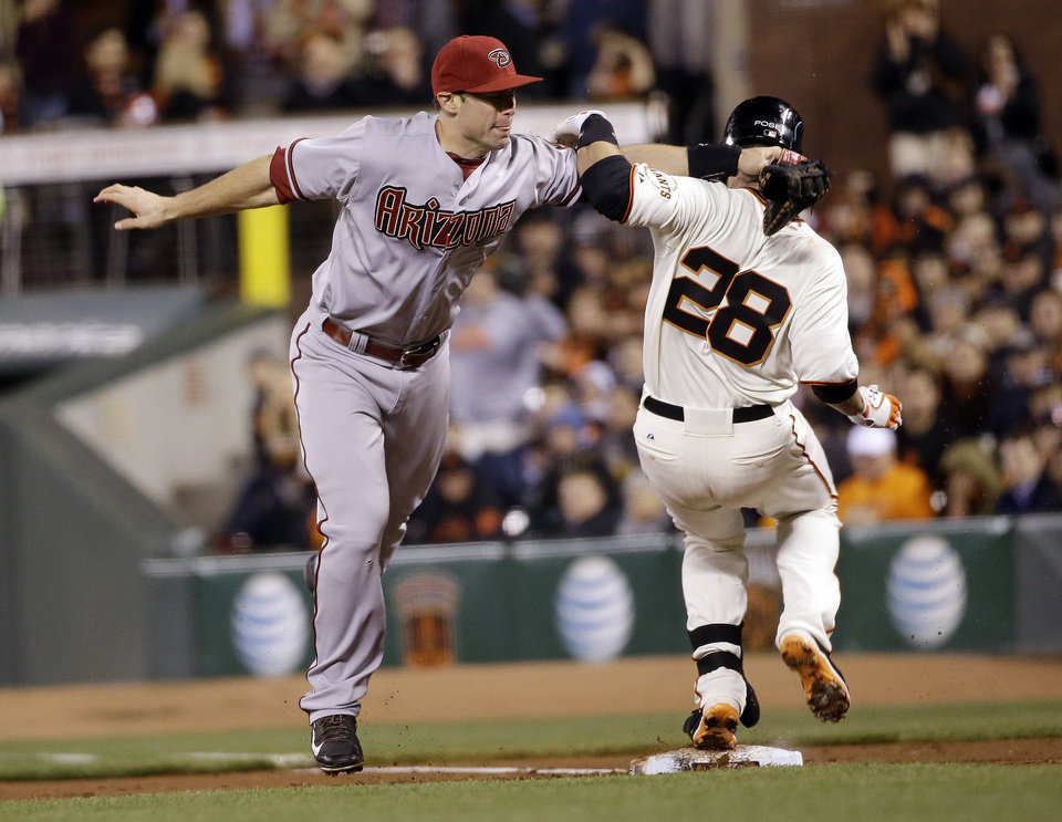 Photo - San Francisco Giants' Buster Posey (28) reaches first base safely on a bunt-single as he becomes entangled with Arizona Diamondbacks first baseman Paul Goldschmidt, left, during the third inning of a baseball game on Thursday, April 10, 2014, in San Francisco. Posey drove in a run with the single. (AP Photo/Marcio Jose Sanchez)