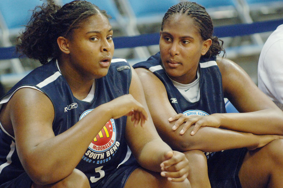 Photo - Courtney (L) and Ashley Paris (R) sit on the bench watching  during a scrimmage which was a prelude to the 2005 McDonald's All American High School Basketball Game  in South Bend, Indiana, March 29, 2005.  HO-MCDONALD'S/Henny Ray Abrams