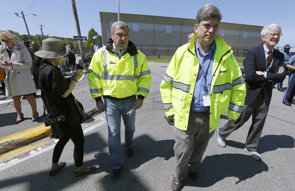 Photo - Massachusetts Port Authority Director of Aviation Ed Freni, center left; Director of Media Relations Matthew Brelis, center, and CEO Thomas P. Glynn, right, walk back to the civil aviation terminal after speaking with reporters at Hanscom Field in Bedford, Mass., Sunday, June 1, 2014. Seven people were killed, including Philadelphia Inquirer co-owner Lewis Katz, in a fiery plane crash as the aircraft was leaving Hanscom Field Saturday night. (AP Photo/Michael Dwyer)