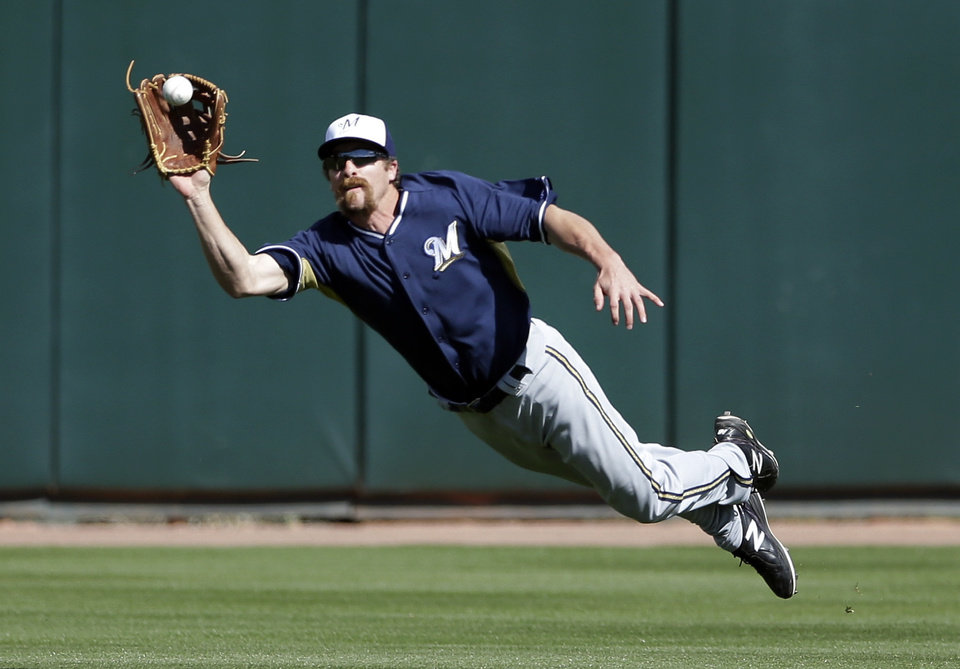 Photo - Milwaukee Brewers center fielder Kevin Mattison makes the catch for the out on a fly ball hit by Oakland Athletics' Daric Barton during the fourth inning of a spring training baseball game Thursday, Feb. 27, 2014, in Scottsdale, Ariz. (AP Photo/Gregory Bull)