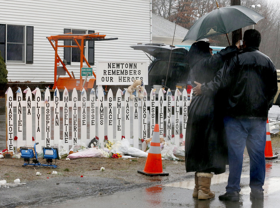 Photo - A woman, left, wipes tears off a man as they pay respects in front of a makeshift memorial before the couple joined fire officials for a moment of silence at 9:30 a.m. Friday, Dec. 21, 2012, in Newtown, Conn. Officials say the gunman, Adam Lanza, killed his mother, Nancy Lanza, at their home before heading to the school.  The chiming of bells reverberated throughout Newtown, commemorating one week since the crackle of gunfire in a schoolhouse killed 20 children and six adults in a massacre that has shaken the community and the nation. (AP Photo/Julio Cortez)