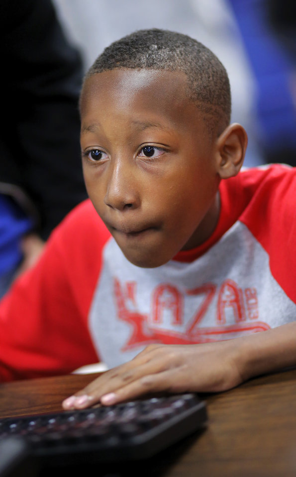 Photo -  Camron Richardson, a fourth-grader at Plaza Towers Elementary in the Moore school district, checks out one of the video games created for Plaza Towers students by Central Junior High students enrolled in video game design classes. Photo by Jim Beckel, The Oklahoman   Jim Beckel -  THE OKLAHOMAN