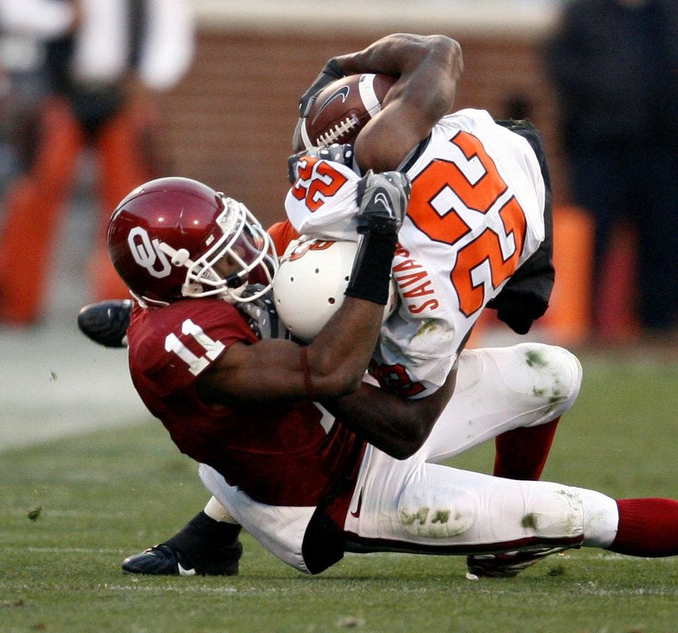 Photo - Lendy Holmes (11) brings down Dantrell Savage (22) during the second half of the college football game between the University of Oklahoma Sooners (OU) and the Oklahoma State University Cowboys (OSU) at the Gaylord Family-Memorial Stadium on Saturday, Nov. 24, 2007, in Norman, Okla. 