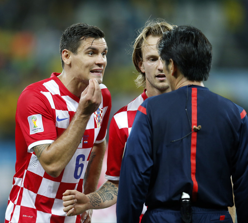 Photo - Croatia's Dejan Lovren, left, and teamamte Ivan Rakitic, center, complain to referee Yuichi Nishimura, from Japan, after Nishimura issued a penalty against Croatia during the group A World Cup soccer match between Brazil and Croatia in the opening game of the tournament at Itaquerao Stadium in Sao Paulo, Brazil, Thursday, June 12, 2014. Brazil's Neymar scored on a penalty kick following the ball helping his team to a 3-1 victory. (AP Photo/Frank Augstein)