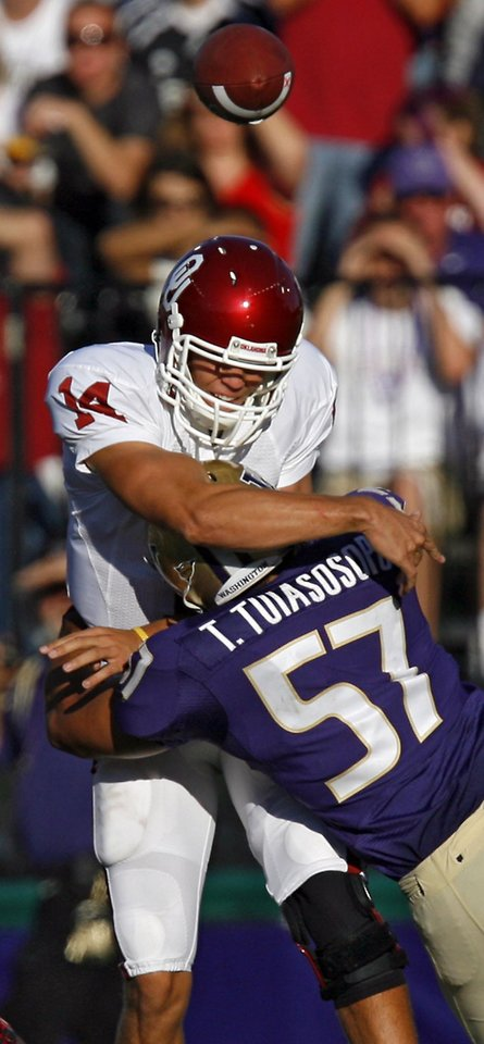 Photo - Oklahoma's Sam Bradford (14) take a hit from Washington's Trenton Tuiasosopo (57) during the first half of the college football game between the University of Oklahoma Sooners (OU) and the University of Washington Huskies (UW) at Husky Stadium on Saturday, Sep. 13, 2008, in Seattle, Wash. 