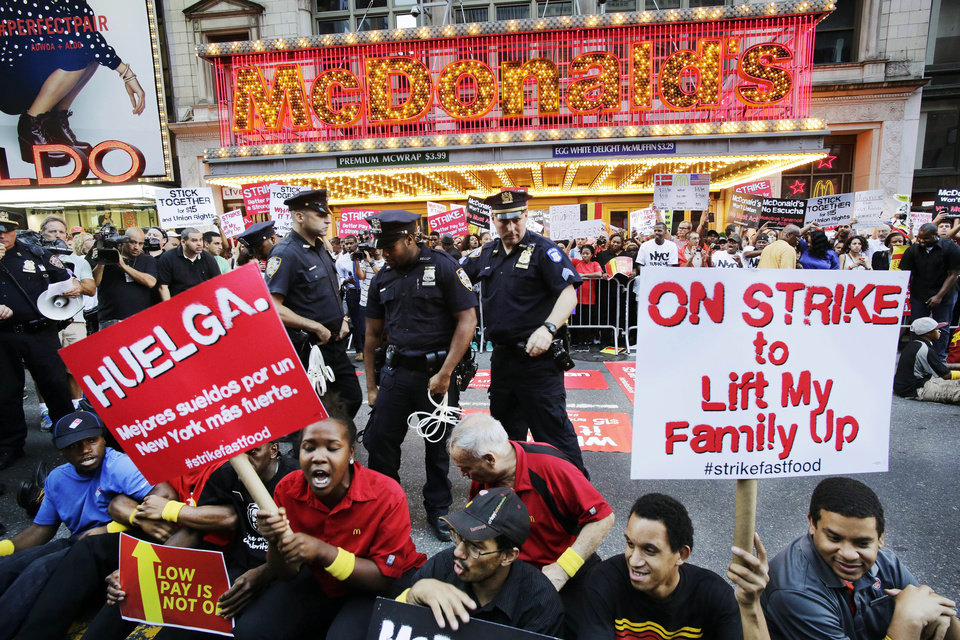 Photo - Protesters sit in front of a McDonald's restaurant on 42nd Street in New York's Times Square as police officers move in to begin making arrests, Thursday, Sept. 4, 2014. The protesters are seeking to get pay increases to $15 per hour. Thursday's demonstration is part of a day of planned protests in 150 cities across the country by workers from fast-food chains. (AP Photo/Mark Lennihan)