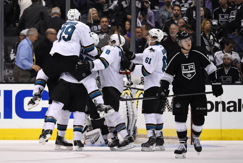 Photo - Members of the San Jose Sharks, left, celebrate a game-winning goal by center Patrick Marleau as Los Angeles Kings center Tyler Toffoli, right, looks on during the overtime period in Game 3 of an NHL hockey first-round playoff series, Tuesday, April 22, 2014, in Los Angeles. The Sharks won 4-3. (AP Photo/Mark J. Terrill)