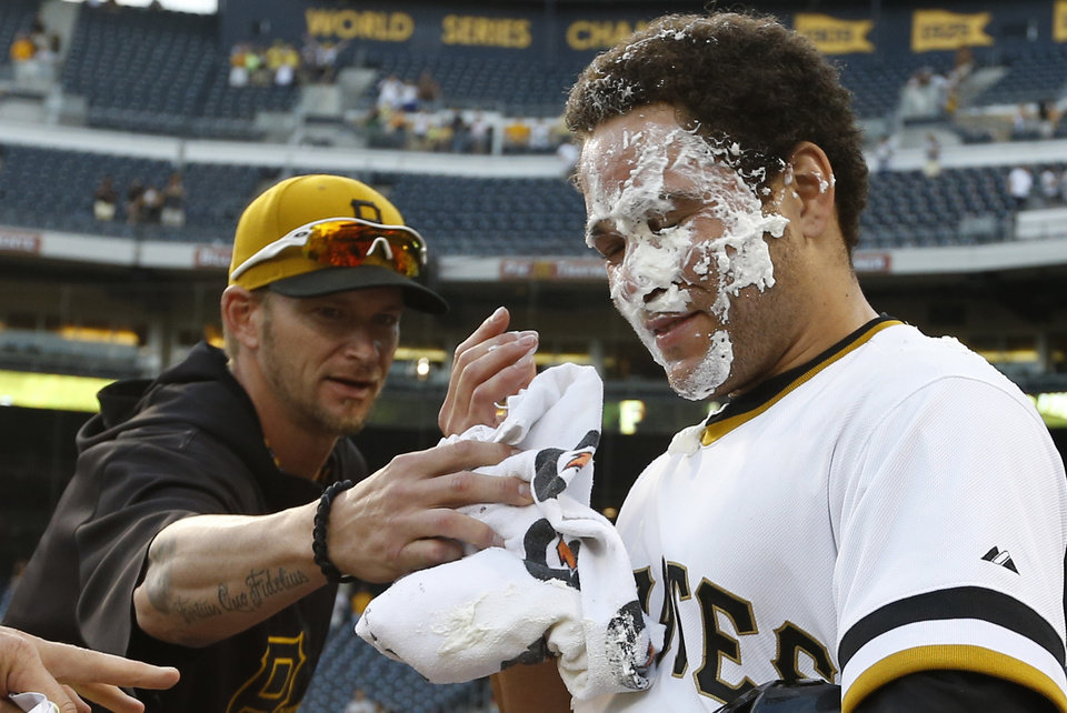 Photo - Pittsburgh Pirates' Russell Martin (55) gets a face full of cream from a towel in celebration from Pittsburgh Pirates'  A.J. Burnett after Martin drove in Gaby Sanchez with the game-winning hit in the 14th inning of the baseball game against the Milwaukee Brewers on Sunday, June 30, 2013, in Pittsburgh. The Pirates won 2-1 in 14 innings. (AP Photo/Keith Srakocic)