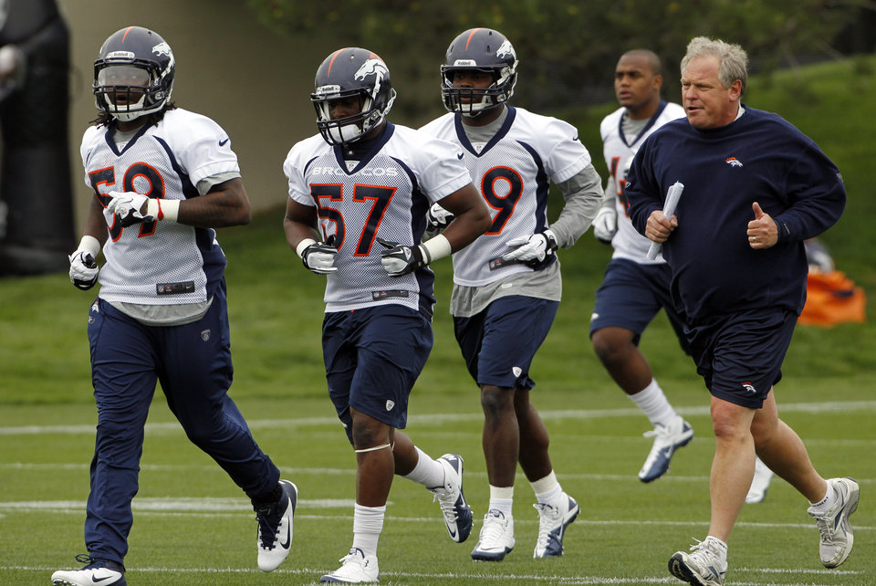 Photo -   Denver Broncos linebackers coach Richard Smith, right, runs with players during the Denver Broncos NFL football rookie minicamp at the team's training facility in Englewood, Colo., on Friday, May 11, 2012. From left are: Danny Trevathan (59), Steven Johnson (57), Jerry Franklin (49) and Elliot Coffey (48). (AP Photo/Ed Andrieski)