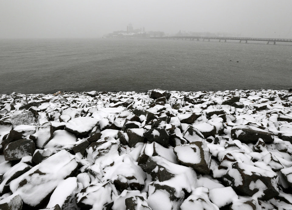 Photo - Sideways snow cuts the visibility of Ellis Island, top, seen from Liberty State Park, as a storm moves into the region, Tuesday, Jan. 21, 2014, in Jersey City, N.J. Ellis Island was set tho host New Jersey Gov. Chris Christie's inauguration party, but hazardous conditions are expected, forcing the party to be canceled. Celebrations to mark the start of Christie's second term could be tempered by investigations into traffic tie-ups that appear to have been ordered by his staff for political retribution and an allegation that his administration linked Superstorm Sandy aid to approval for a real estate project. (AP Photo/Julio Cortez)
