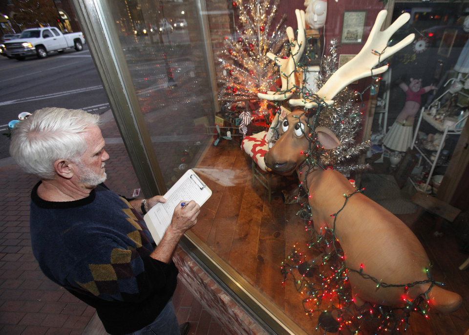 Bob Palmer, from the University of Central Oklahoma, judges the downtown business windows that are decorated for Christmas. PHOTO BY DAVID MCDANIEL, THE OKLAHOMAN. <strong>David McDaniel - THE OKLAHOMAN</strong>