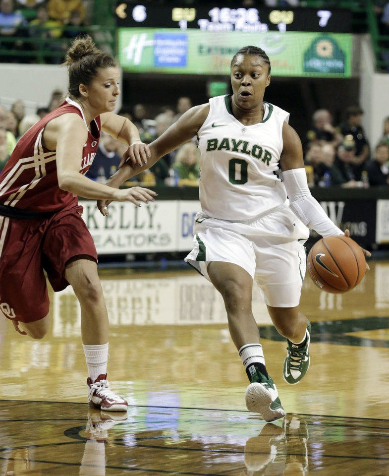 Photo - Baylor's Odyssey Sims (0) drives the lane against Oklahoma's Morgan Hook, left, during the first half of an NCAAcollege basketball game Saturday, Jan. 26, 2013,. in Waco Texas. (AP Photo/LM Otero) ORG XMIT: TXMO102