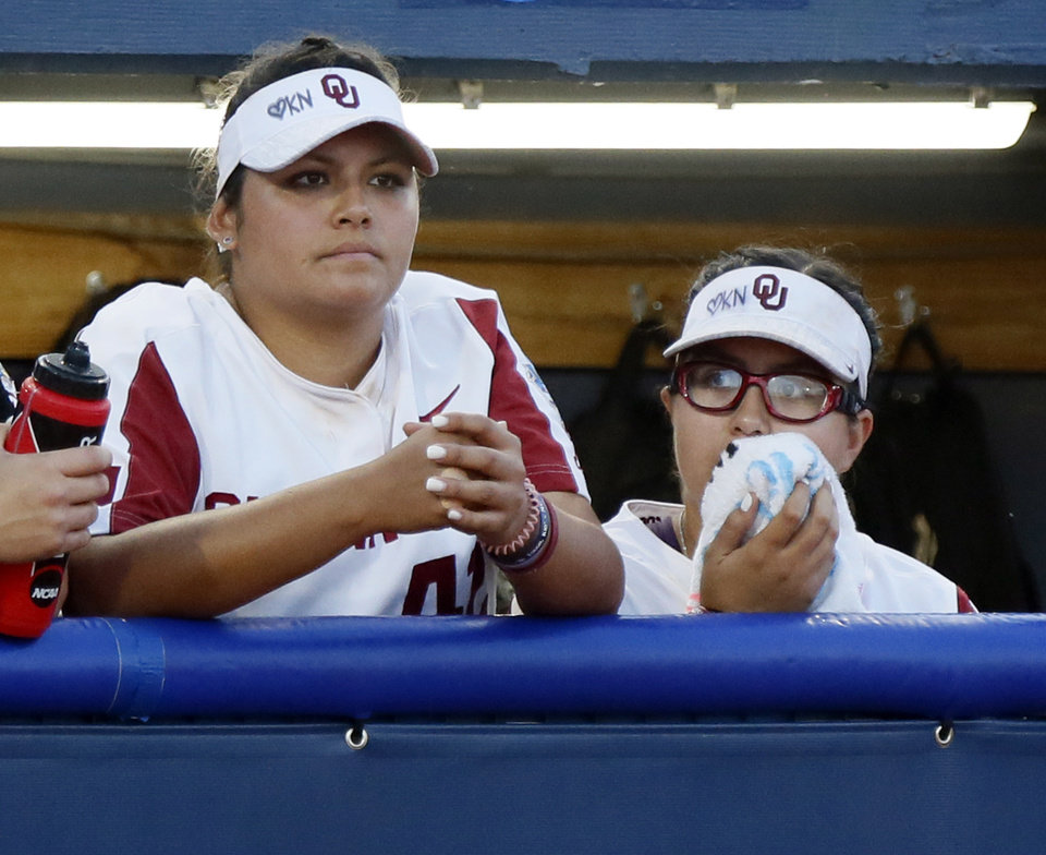 Photo - OU pitchers Mariah Lopez (42), left, and Giselle Juarez (45) watch from the dugout in the sixth inning during the first NCAA softball game in the championship series of the Women's College World Series between Oklahoma and UCLA at USA Softball Hall of Fame Stadium in Oklahoma City, Monday, June 3, 2019. [Nate Billings/The Oklahoman]