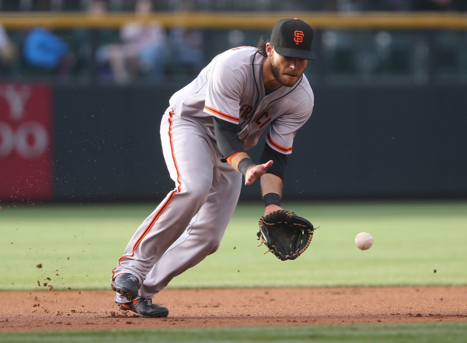 Photo - San Francisco Giants shortstop Brandon Crawford fields ground ball off the bat of Colorado Rockies' Troy Tulowitzki in the first inning of a baseball game in Denver on Wednesday, May 21, 2014. (AP Photo/David Zalubowski)