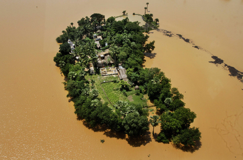Photo - AP10ThingsToSee - An aerial view shows houses cut-off by monsoon floods in Kendrapara district of eastern Orissa state, India, Wednesday, Aug. 6, 2014. (AP Photo/Biswaranjan Rout)
