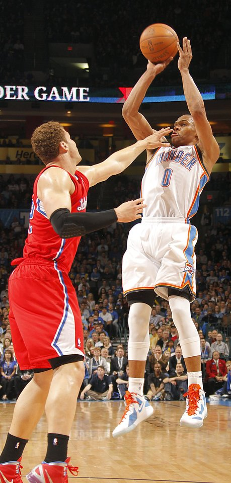 Photo - Oklahoma City Thunder point guard Russell Westbrook (0) shoots over Los Angeles Clippers power forward Blake Griffin (32) during the NBA basketball game between the Oklahoma City Thunder and the Los Angeles Clippers at Chesapeake Energy Arena on Wednesday, March 21, 2012 in Oklahoma City, Okla.  Photo by Chris Landsberger, The Oklahoman