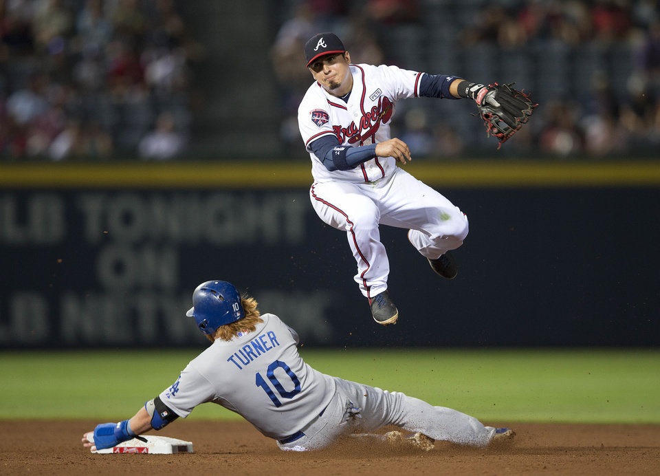 Photo - Atlanta Braves second baseman Ramiro Pena (14) avoids Los Angeles Dodgers' Justin Turner (10) as he tries to turn a double play on a  A.J. Ellis ground ball in the eighth inning of a baseball game  Monday, Aug. 11, 2014 in Atlanta. Ellis was safe at first allowing a run to score.  (AP Photo/John Bazemore)