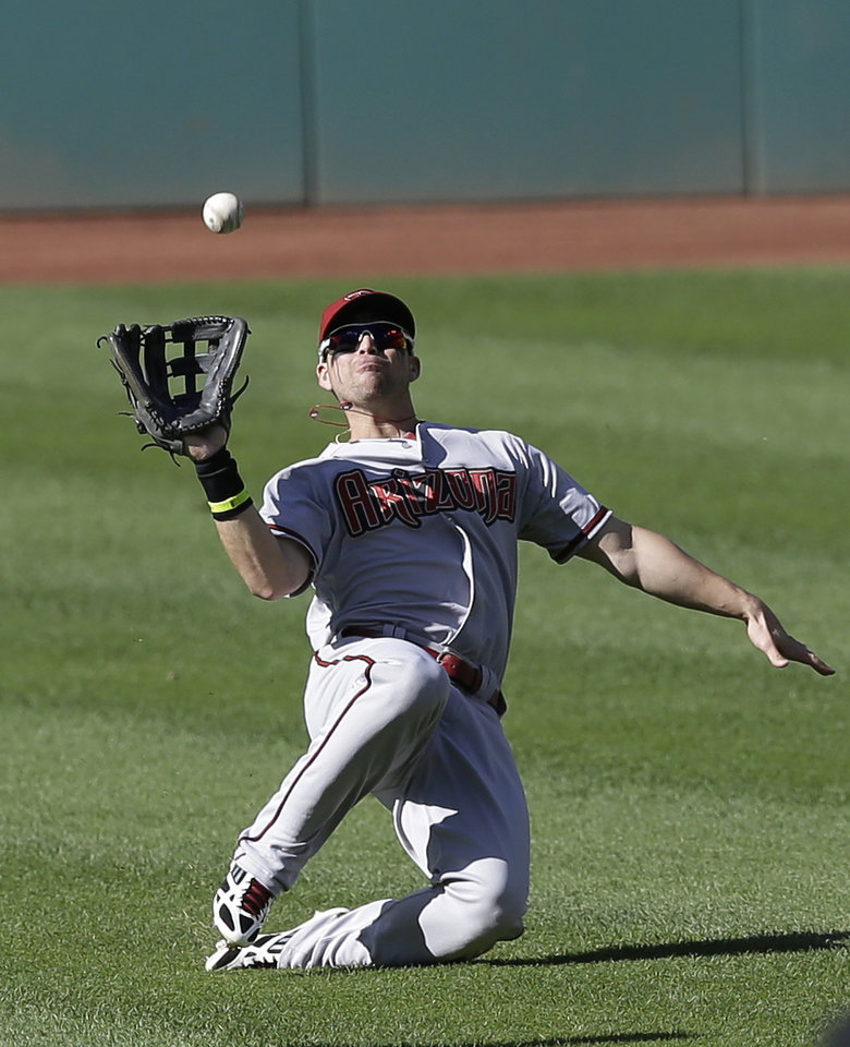 Photo - Arizona Diamondbacks' Ender Inciarte dives for a ball hit by Cleveland Indians' Lonnie Chisenhall (8) in the fifth inning of the first baseball game of a doubleheader, Wednesday, Aug. 13, 2014, in Cleveland. Chisenhall was out on the play. (AP Photo/Tony Dejak)