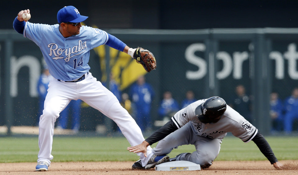 Photo - Kansas City Royals second baseman Omar Infante (14) forces out Chicago White Sox' Marcus Semien during the first inning of a baseball game at Kauffman Stadium in Kansas City, Mo., Sunday, April 6, 2014. Semien was out by fielder's choice. (AP Photo/Orlin Wagner)