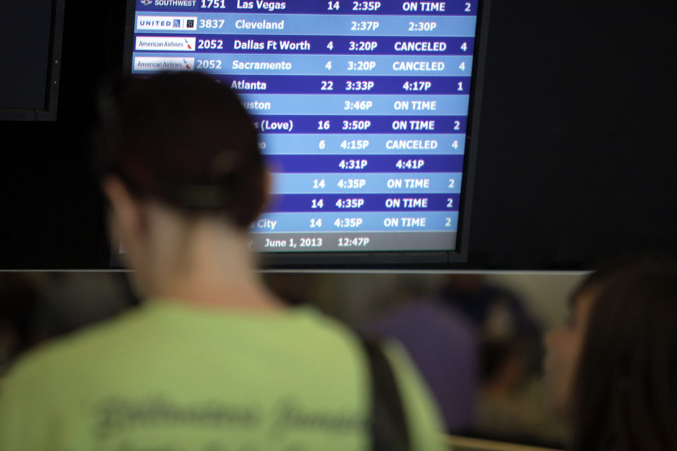 People watch flight schedules updating in the terminal of Will Rogers Airport as cleanup continues after the May 31, 2013 tornadoes in Oklahoma City. Photo by KT KING, The Oklahoman