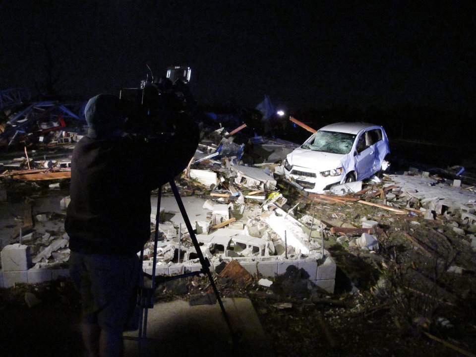 Photo - A news cameraman shoots video of the rubble of an auto parts store destroyed by a tornado in Washington, Ill., on Sunday, Nov. 17, 2013. Illinois State Police says everal people were inside at the time the tornado hit but all escaped uninjured. The tornado cut a path of destruction through Washington. (AP Photo/David Mercer)