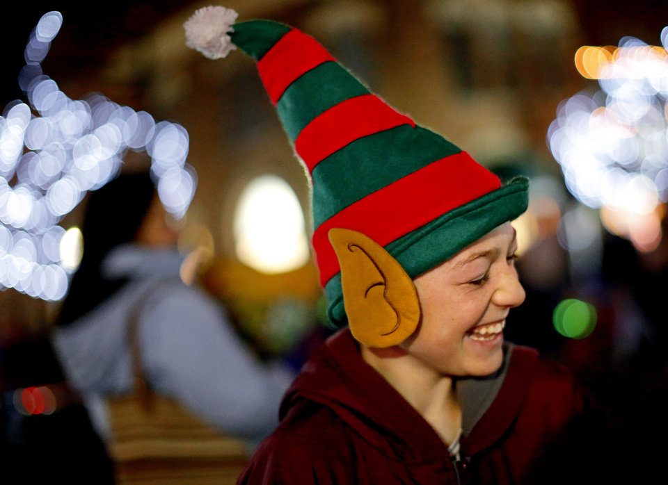 Photo - Paul Davis, 11, laughs Saturday during the Edmond Electric Parade of Lights in downtown Edmond.