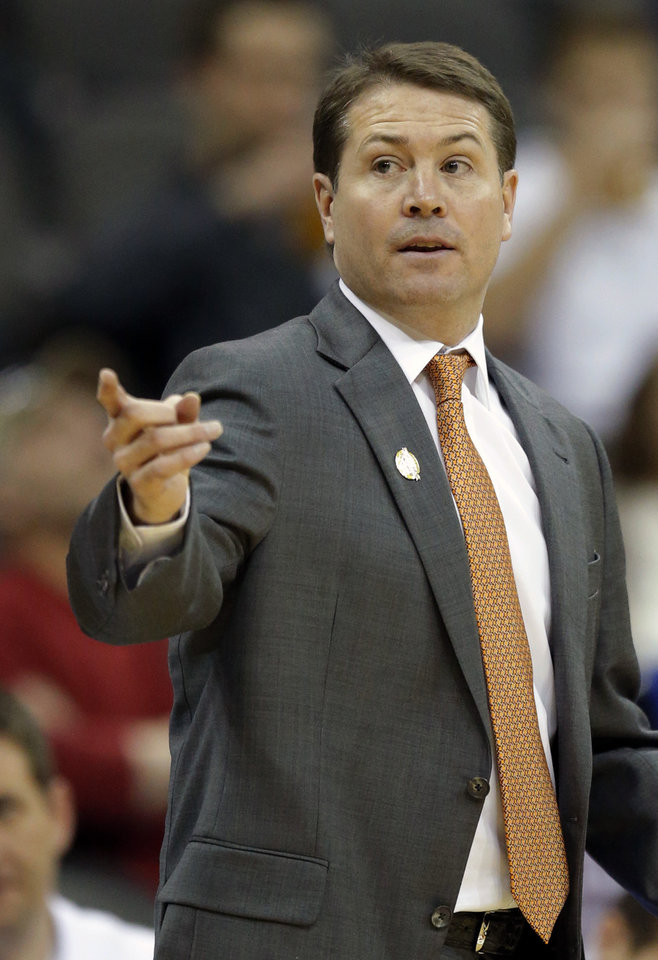 Photo - Oklahoma State head coach Travis Ford directs his team during the first half of an NCAA college basketball game against Texas Tech in the Big 12 men's tournament in Kansas City, Mo., Wednesday, March 12, 2014. (AP Photo/Orlin Wagner)
