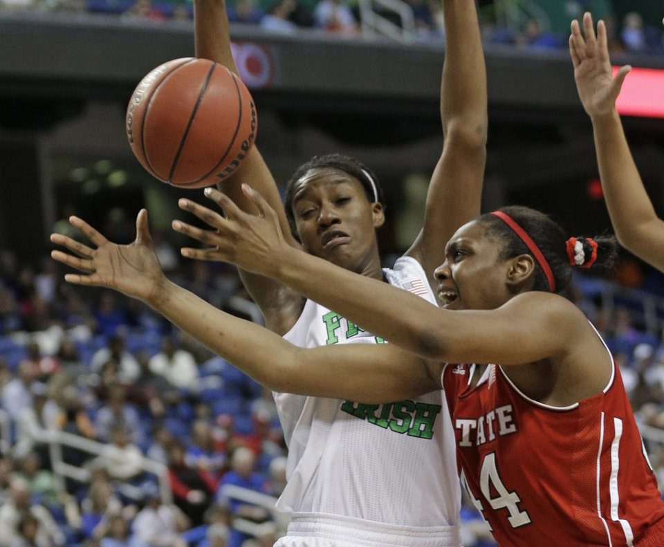 Photo - North Carolina State's Kody Burke, right, loses the ball as Notre Dame's Markisha Wright, left, defends during the first half of an NCAA college basketball semifinal game at the Atlantic Coast Conference tournament in Greensboro, N.C., Saturday, March 8, 2014. (AP Photo/Chuck Burton)