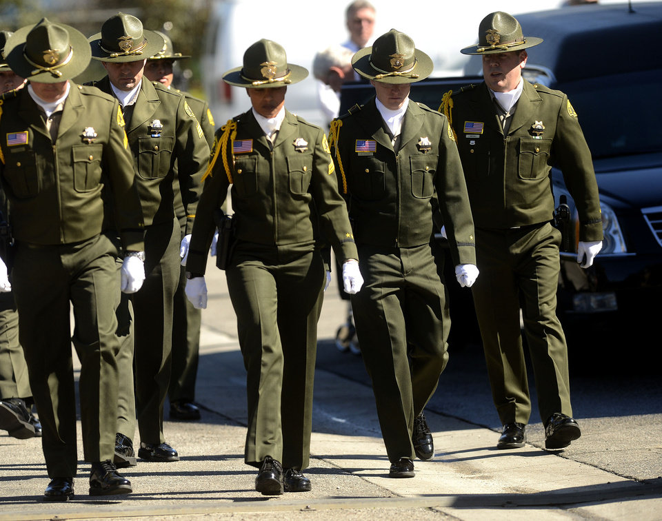 An honor guard walks away after loading the casket of slain San Bernardino County Sheriff's Deputy Jeremiah MacKay into a hearse at the SBCO Coroner's Office in San Bernardino, Calif. on Thursday, Feb. 14, 2013. MacKay was killed in a shootout outside the cabin in Big Bear, Calif. where fugitive ex-cop Christopher Dorner was barricaded inside. The Department held a small service with Honor Guard, and the playing of bag pipes prior to a procession led by a motorcade to Mountain View Mortuary in San Bernardino. (AP Photo/The Sun, Gabriel Luis Acosta)  VENTURA COUNTY STAR OUT; RIVERSIDE PRESS-ENTERPRISE OUT; THE VICTOR VALLEY DAILY PRESS OUT