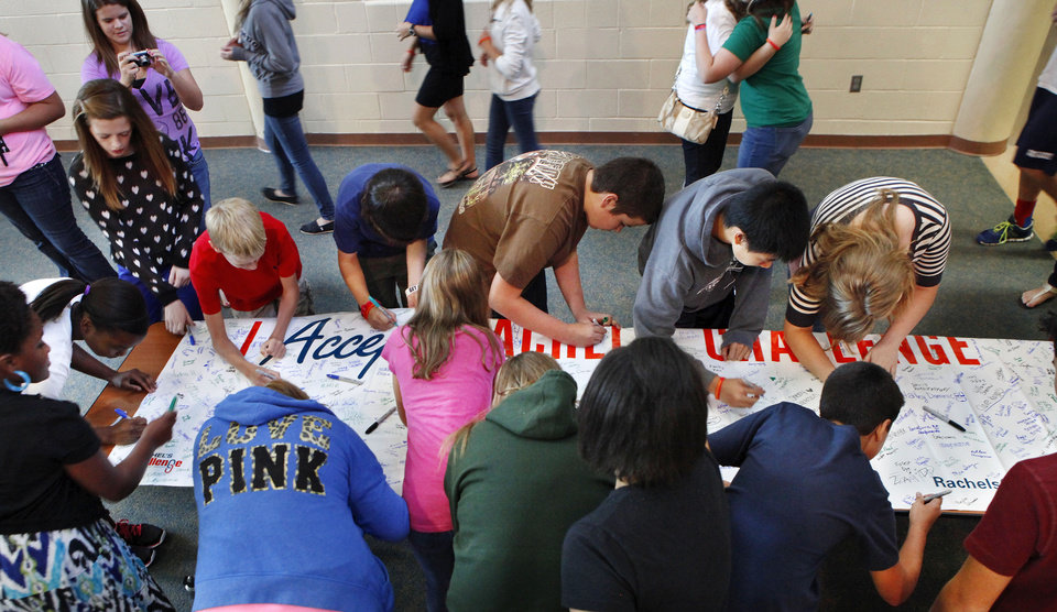 Photo - Eighth-grade students from Cheyenne Middle School sign the Rachel's Challenge pledge banner.  Photo by Jim Beckel, The Oklahoman  Jim Beckel - THE OKLAHOMAN