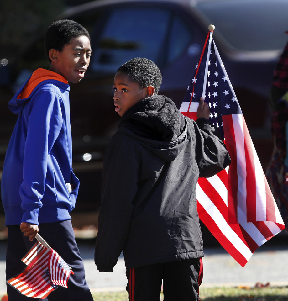Boys from Soldier Creek Elementary School carry American flags back to their classroom after watching the parade. The city of Midwest City teamed with civic leaders and local merchants to display their appreciation for veterans and active military forces by staging a hour-long Veteran's Day parade that stretched more than a mile and a half along three of the city's busiest streets Monday morning, Nov. 12, 2012. Hundreds of people lined the parade route, many of them waving small American flags that had ben distributed by volunteers who marched near the front of the parade. A fly-over performed by F-16s from the138th Fighter Wing, Oklahoma Air National Guard unit in Tulsa thrilled spectators. Five veterans representing military personnel who served in five wars and military actions served as  Grand Marshals for the parade. Leading the parade was the Naval Reserve seven-story American flag, carried by 100 volunteers from First National Bank of Midwest City, Advantage Bank and the Tinker Federal Credit Union. The flag is 50 feet by 76 feet, weighs 110 pounds and was sponsored by the MWC Chapter of Disabled American Veterans. Photo by Jim Beckel, The Oklahoman