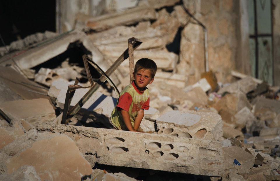 Photo -   FILE - In a Tuesday, June 5, 2012 file photo, a Syrian boy sits in the rubble of house which was destroyed during a military operation by the Syrian army in April 2012, in the town of Taftanaz, 15 kilometers east of Idlib, Syria. (AP Photo/Khalil Hamra, File)