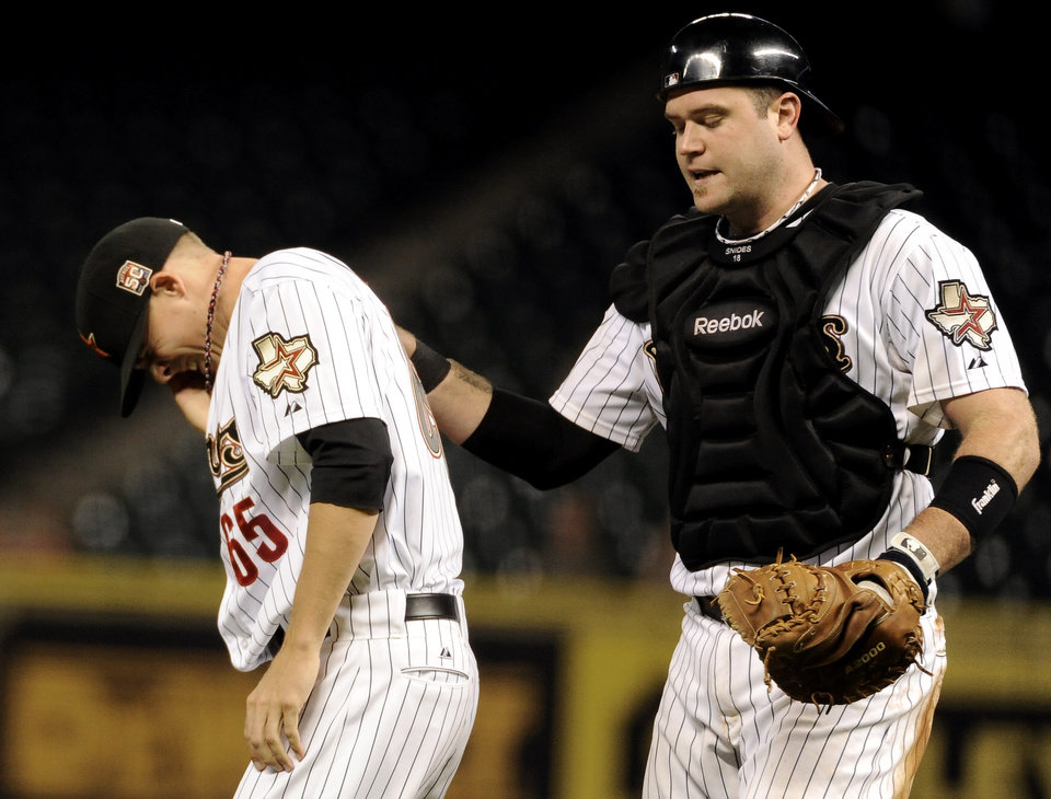 Photo -   Houston Astros catcher Chris Snyder, right, checks on relief pitcher Mickey Storey (65) after he was hit in the face by a line drive from Chicago Cubs' Dave Sappelt in the eighth inning of a baseball game Wednesday, Sept. 12, 2012, in Houston. (AP Photo/Pat Sullivan)