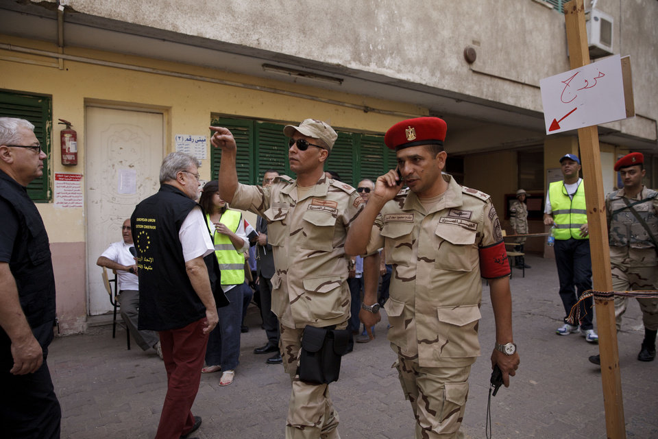 Photo - An election observer from the European Union, second left, visits a polling station as Egyptian security forces patrol in an election that comes nearly a year after the military's ouster of the nation's first freely elected president, the Islamist Mohammed Morsi, in Cairo, Egypt, Monday, May 26, 2014. The man who removed Morsi, retired military chief Field Marshal Abdel-Fattah el-Sissi, is practically assured of a victory in the vote. Arabic on sign reads,