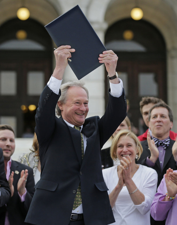 Photo - Rhode Island Gov. Lincoln Chafee holds up a a gay marriage bill after signing it into law outside the State House in Providence, R.I., Thursday, May 2, 2013. (AP Photo/Charles Krupa)