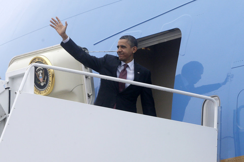 Photo - President Barack Obama turns and waves as he boards Air Force One at Andrews Air Force Base, Md., Monday, Dec. 10, 2012, as he travels to Michigan to visit the Daimler Detroit Diesel plant in Redford, Mich. (AP Photo/Charles Dharapak)