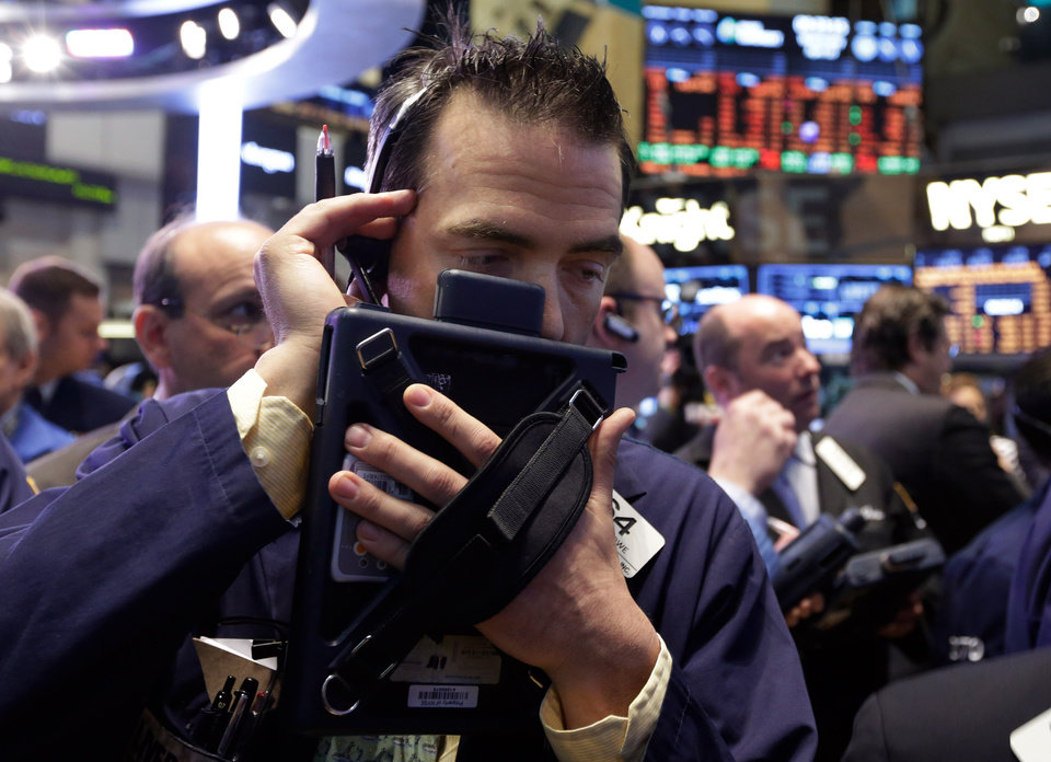 Photo - Trader Gregory Rowe, center, works on the floor of the New York Stock Exchange Wednesday, April 10, 2013. Stocks are opening higher on Wall Street, a day after the Dow Jones industrial average closed at its second all-time high in a week. (AP Photo/Richard Drew)