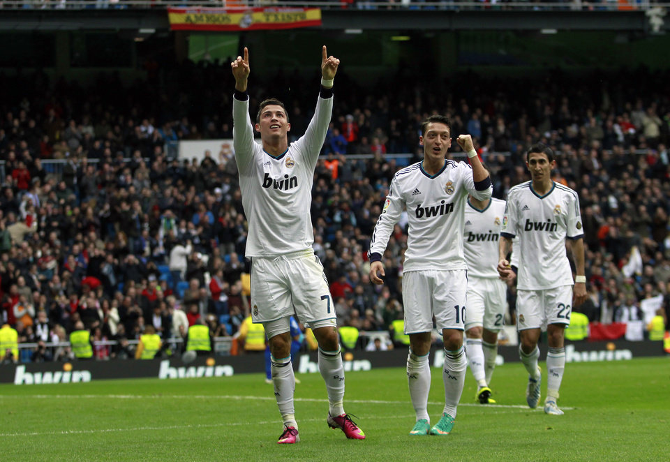 Real Madrid's Cristiano Ronaldo from Portugal, left, celebrates his goal with Mesut Ozil from Germany, center, during a Spanish La Liga soccer match against Getafe at the Santiago Bernabeu stadium in Madrid, Spain, Sunday, Jan. 27, 2013. (AP Photo/Andres Kudacki)