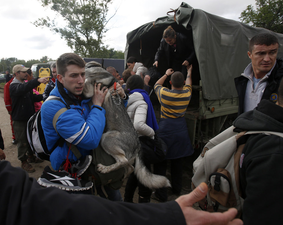 Photo - A man holds his dog during the evacuation from floods in Obrenovac, some 30 kilometers (18 miles) southwest of Belgrade Serbia, Saturday, May 17, 2014. Record flooding in the Balkans leaves at least 20 people dead in Serbia and Bosnia and is forcing tens of thousands to flee their homes. Meteorologists say the flooding is the worst since records began 120 years ago. (AP Photo/Darko Vojinovic)