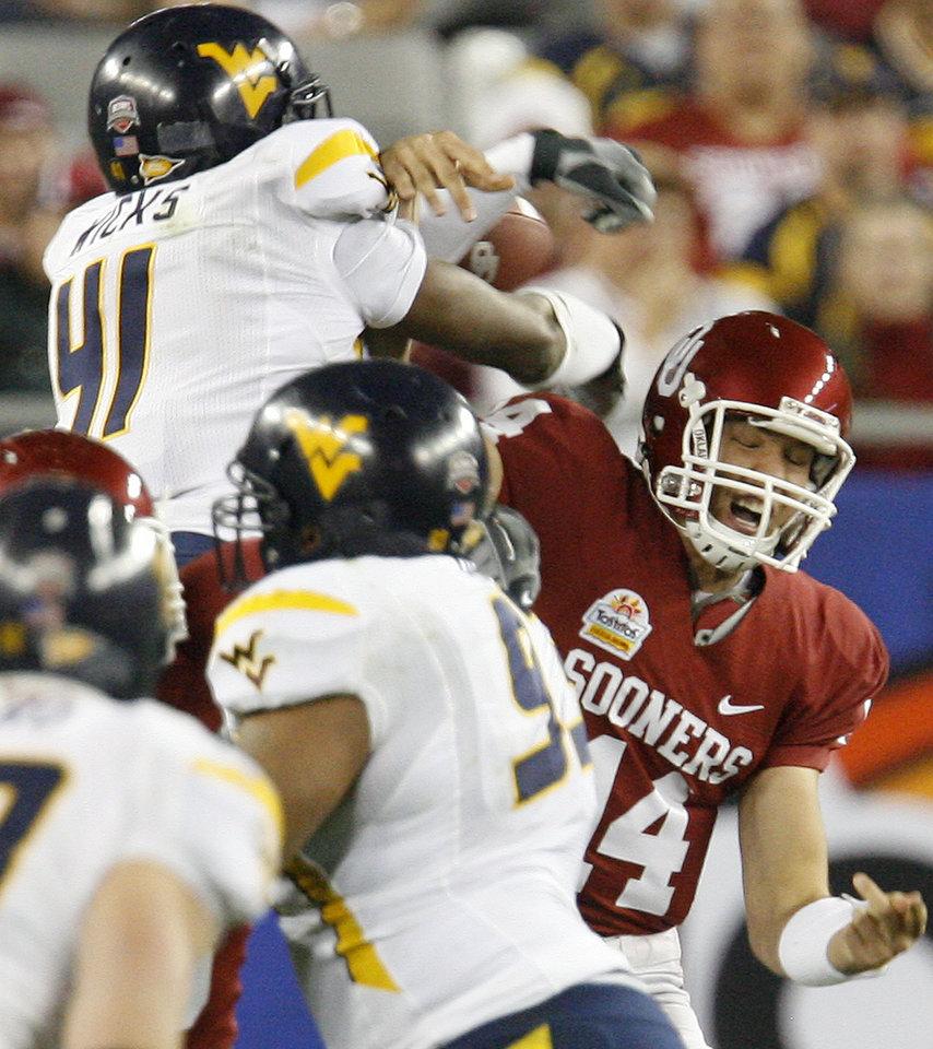 Photo - Oklahoma's Sam Bradford (14) is hit by West Virginia's Eric Ricks (41) during the first half of the Fiesta Bowl college football game between the University of Oklahoma Sooners (OU) and the West Virginia University Mountaineers (WVU) at The University of Phoenix Stadium on Wednesday, Jan. 2, 2008, in Glendale, Ariz. 
