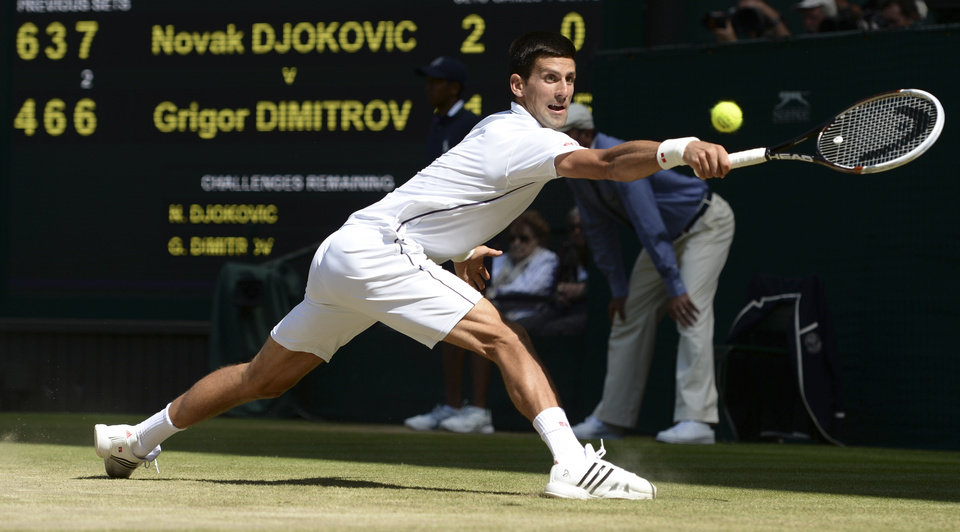 Photo - Novak Djokovic of Serbia stretches to reach a return to Grigor Dimitrov of Bulgaria during their men's singles semifinal match at the All England Lawn Tennis Championships at Wimbledon, London, Friday, July, 4, 2014. (AP Photo/Anthony Devlin, Pool)