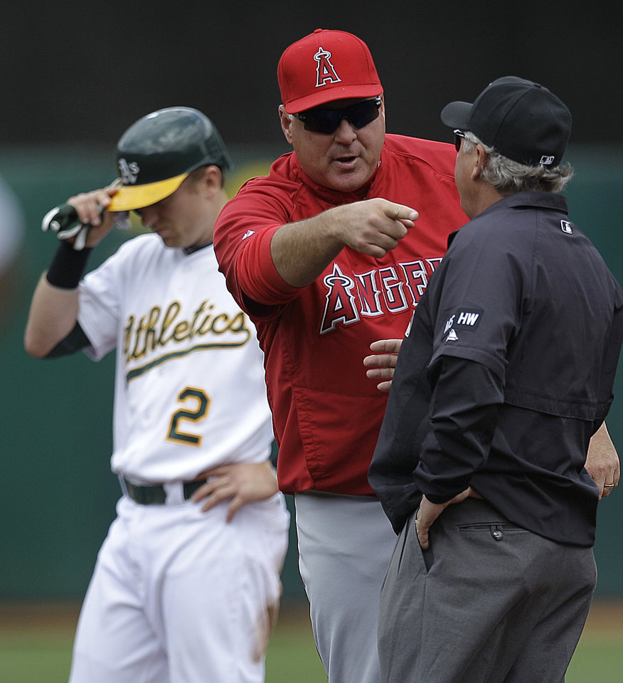 Photo -   Los Angeles Angels manager Mike Scioscia, center, argues a call with second base umpire Tom Hallion, right, in the third inning of a baseball game against the Oakland Athletics, Wednesday, Sept. 5, 2012, in Oakland, Calif. Scioscia argued that A's Cliff Pennington, left, ran outside the baseline en route to second base. (AP Photo/Ben Margot)