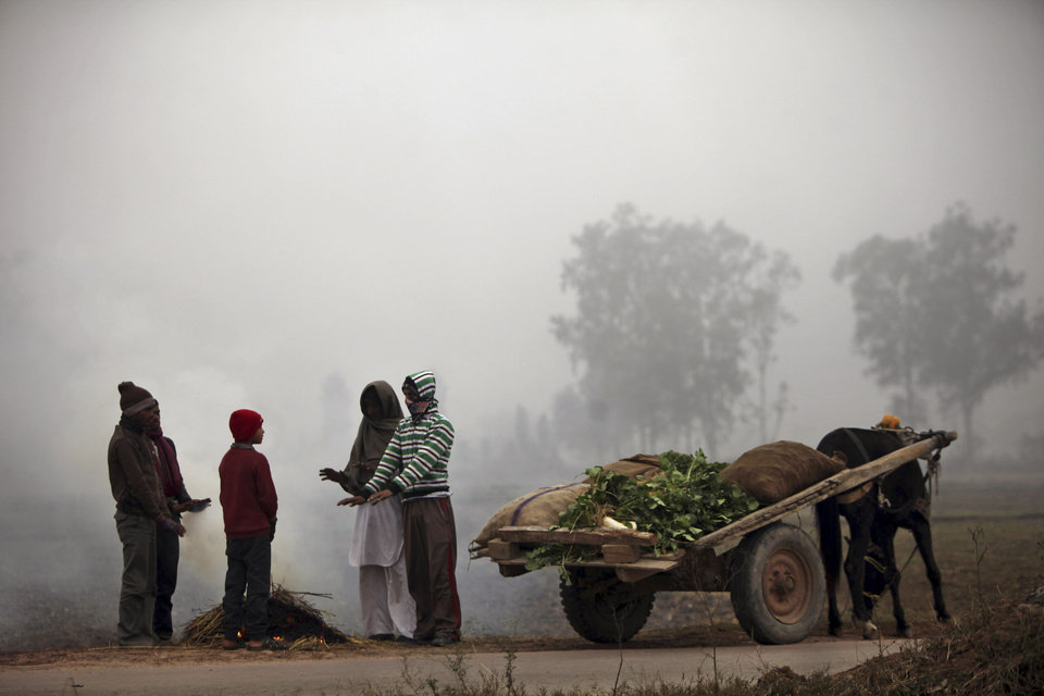 Indian vendors warm themselves near a fire on a cold and foggy morning in Jammu, India, Tuesday, Jan. 8, 2013. North India continues to face below average weather conditions with dense fog affecting flights and trains. More than 100 people have died of exposure as northern India deals with historically cold temperatures. (AP Photo/Channi Anand)
